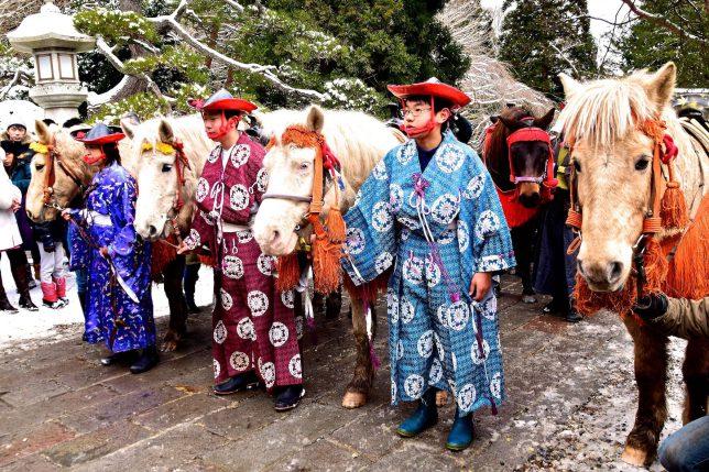 本堂前で参拝をする騎馬