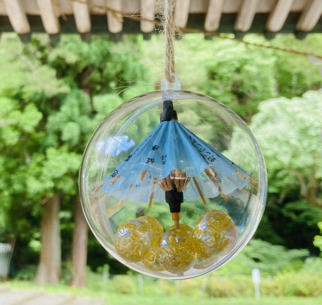 透明な鞠をよく見るとプラスティックカプセルの中に小さな傘と玉が入っていた